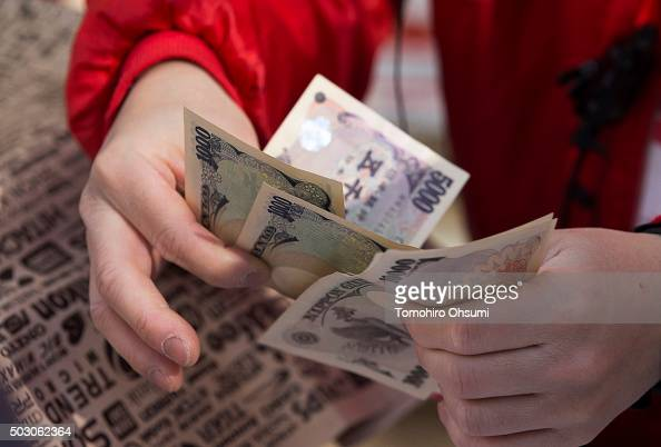 An employee counts Japanese yen notes as he sells a 'lucky bag' at a Bic Camera Inc store on January 1 2016 in Tokyo Japan Many Japanese retail...