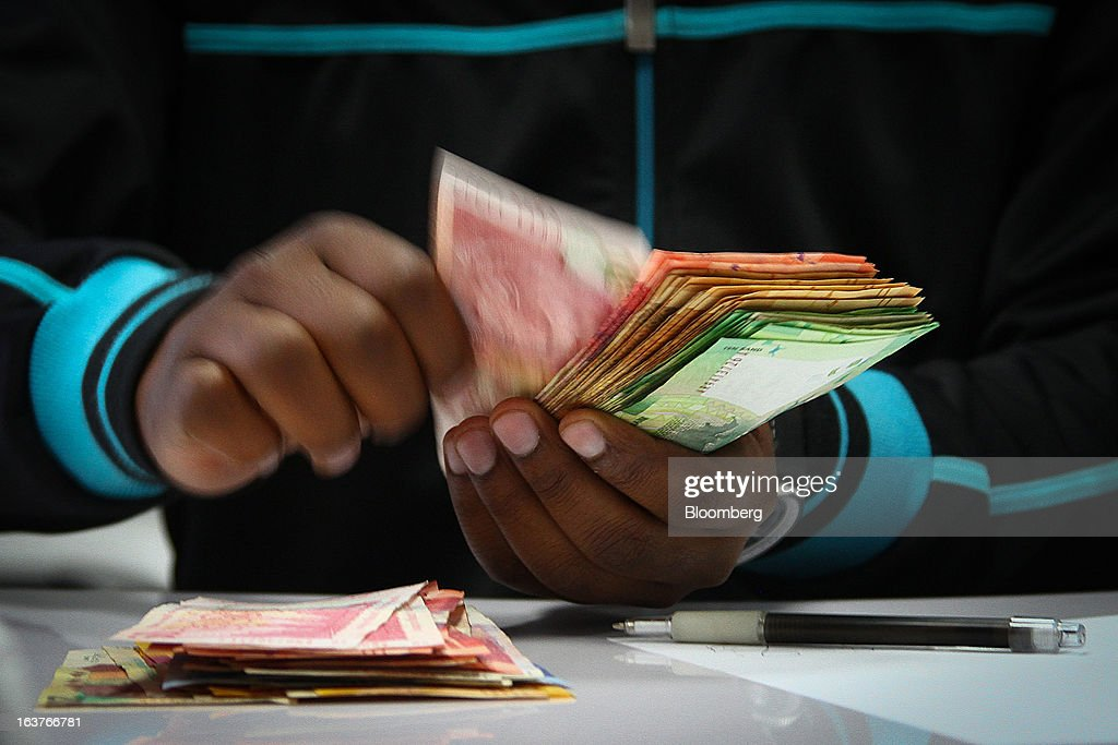 An employee counts mixed denomination rand currency banknotes at the Forex department inside a First National Bank (FNB) branch in Johannesburg, South Africa, on Friday, March 15, 2013. A recovery in mining and manufacturing is giving South Africa's rand and bonds a breather amid concern that growth is slowing while inflation accelerates. Photographer: Nadine Hutton/Bloomberg via Getty Images