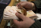 An employee counts out 50 Turkish lira banknotes at a currency exchange office in Istanbul Turkey on Monday Jan 27 2014 The lira appreciated the most...