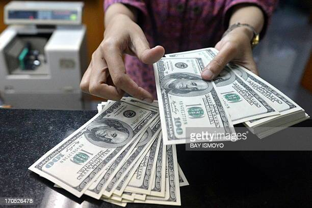 An employee counts USD notes at a money change outlet in Jakarta on June 14 2013 Indonesia's central bank unexpectedly hiked interest rates for the...