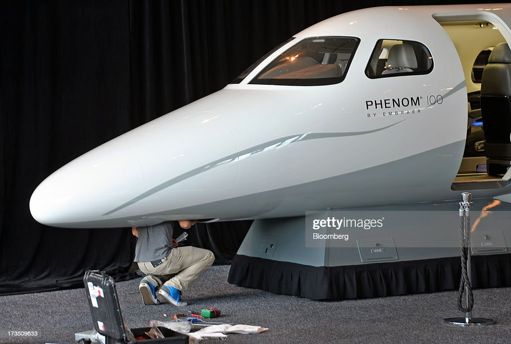 An employee crouches under the nose of a mockup fuselage on an Embraer SA Phenom 100 jet at the company's executive jet manufacturing facility in Melbourne, Florida, U.S., on Monday, July 15, 2013. Embraer SA, the world's largest manufacturer of commercial jets up to 120 seats, delivered 22 jets to the commercial aviation market and 29 to the executive aviation market, for a total of 51 aircraft in the second quarter of 2013, according to a company press release. Photographer: Mark Elias/Bloomberg via Getty Images