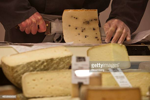 An employee cuts a block of cheese in the Victor Hugo indoor market in Toulouse France on Wednesday Jan 29 2014 Euroregion retail sales increased 14...