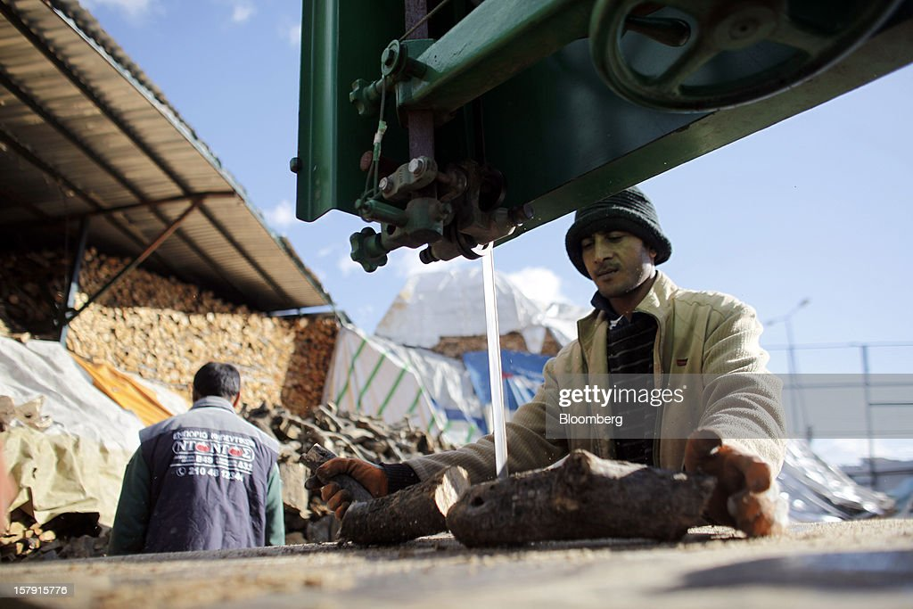 An employee cuts a log to size using a bandsaw in the yard of a wood store in Athens, Greece, on Friday, Dec. 7, 2012. Greece, the epicenter of Europe's debt crisis since revealing a bloated spending gap in late 2009, has faced regular demands to get a firmer grip on the budget or risk being forced out of the euro. Photographer: Kostas Tsironis/Bloomberg via Getty Images