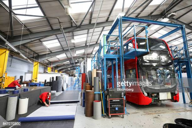 An employee cuts a section of flooring to be used in an Enviro 400 London bus at the Alexander Dennis Ltd factory in Scarborough UK on Wednesday Sept...