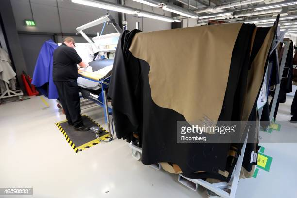 An employee cuts leather sections for the interior upholstery of luxury automobiles at the Rolls Royce Motor Cars Ltd production plant in Goodwood UK...