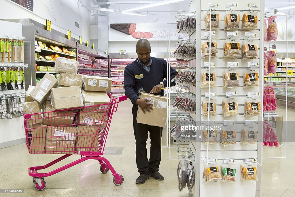 An employee cuts open a box of goods as he restocks a display inside a Game supermarket, part of Massmart Holdings Ltd., in the Fourways district of Johannesburg, South Africa, on Thursday, Aug. 22, 2013. Massmart Holdings Ltd., the South African food and goods wholesaler owned by Wal-Mart Stores Inc., said revenue growth continued to slow in August after a downturn in consumer spending hurt first-half earnings. Photographer: Nadine Hutton/Bloomberg via Getty Images