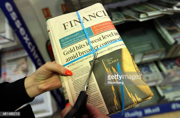 An employee cuts open a bundle of Financial Times newspapers in this arranged photograph at a newsagent store in Danbury Essex UK on Tuesday July...