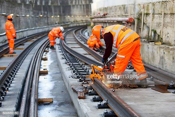 An employee cuts through a length of steel track close to the Crossrail Connaught tunnel in London UK on Tuesday Dec 8 2015 Crossrail the UK...