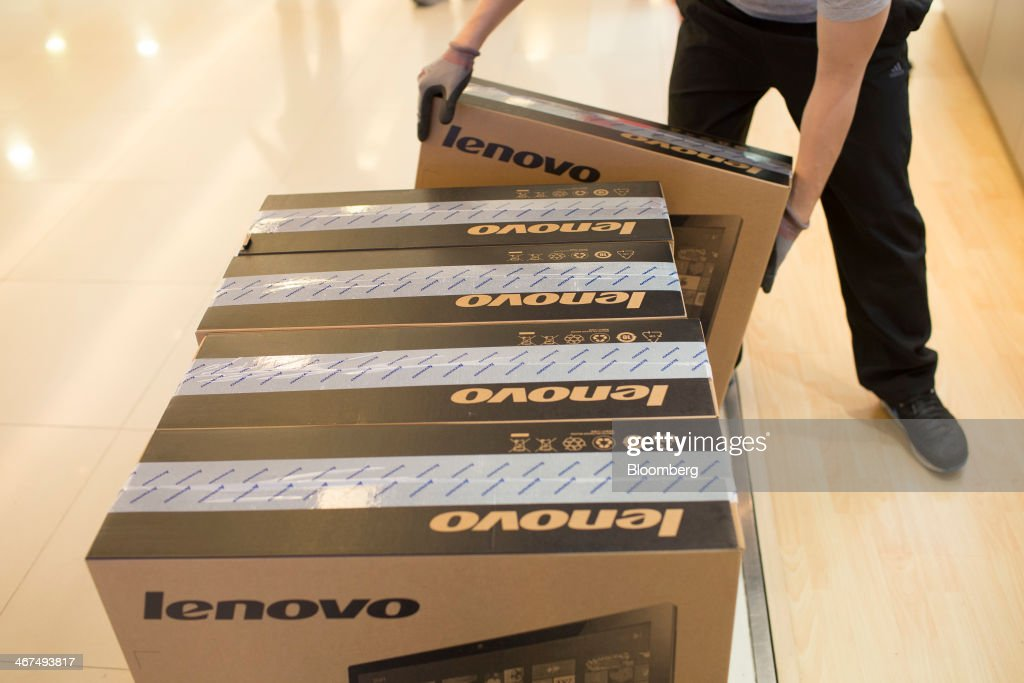 An employee delivers Lenovo Group Ltd. computers at a Lenovo store in the Sha Tin district of Hong Kong, China, on Friday, Feb. 7, 2014. Lenovo, which has headquarters in Beijing and Morrisville, North Carolina, agreed to pay $2.3 billion for IBMs low-end server unit on Jan. 23, adding a business with wider profit margins than PCs and giving it about 14 percent of the market. Photographer: Brent Lewin/Bloomberg via Getty Images
