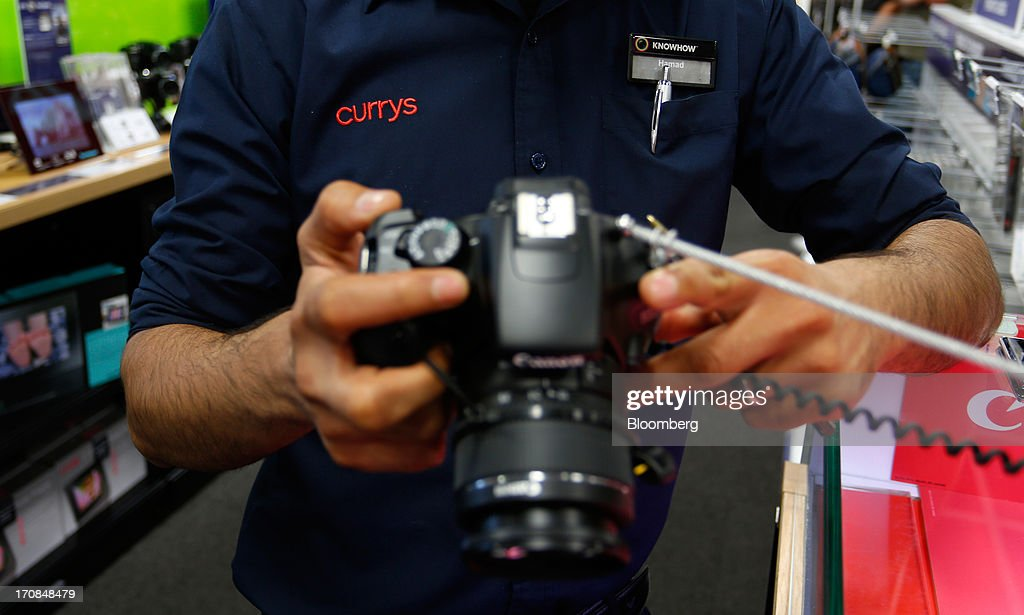 An employee demonstrates a Canon Inc. digital camera inside a Currys and PC World 2 in 1 store, operated by Dixons Retail Plc, in Manchester, U.K., on Tuesday, June 18, 2013. Dixons Retail Plc, the U.K.'s largest consumer-electronics retailer, said last month it will report annual pretax profit at the 'top end' of analysts' predictions after fourth-quarter revenue beat estimates on increased sales of tablets and services such as software tutorials. Photographer: Paul Thomas/Bloomberg via Getty Images
