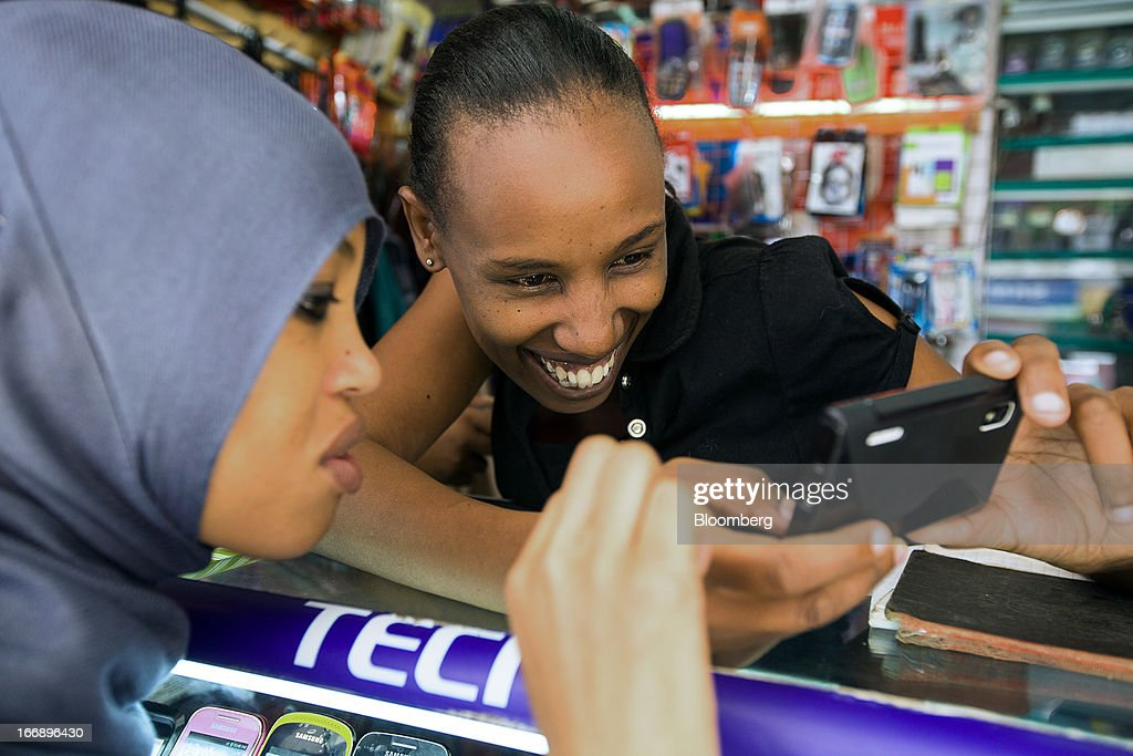 An employee demonstrates a mobile handset to a customer at the counter of a phone store in Nairobi, Kenya, on Wednesday, April 17, 2013. Though only 23 percent of houses there have electricity and just 9 percent of roads are paved, mobile-phone penetration is 75 percent in the country, up from 5 percent in 2003. Photographer: Trevor Snapp/Bloomberg via Getty Images
