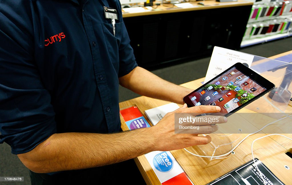 An employee demonstrates an Apple Inc. iPad inside a Currys and PC World 2 in 1 store, operated by Dixons Retail Plc, in Manchester, U.K., on Tuesday, June 18, 2013. Dixons Retail Plc, the U.K.'s largest consumer-electronics retailer, said last month it will report annual pretax profit at the 'top end' of analysts' predictions after fourth-quarter revenue beat estimates on increased sales of tablets and services such as software tutorials. Photographer: Paul Thomas/Bloomberg via Getty Images