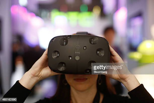 An employee demonstrates an HTC Vibe VR virtual reality headset in the HTC Corp pavilion at the Mobile World Congress in Barcelona Spain on Tuesday...