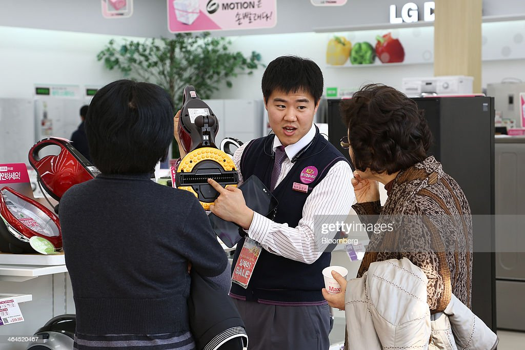 An employee demonstrates an LG Electronics Inc. bedding cleaner for customers at the company's Bestshop store in Seoul, South Korea, on Wednesday, Jan. 22, 2014. LG Electronics, the worlds second-largest seller of televisions, is scheduled to announce fourth-quarter earnings on Jan. 27. Photographer: SeongJoon Cho/Bloomberg via Getty Images