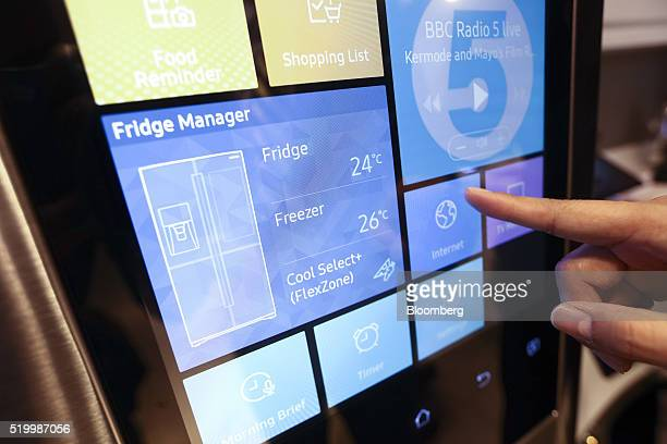An employee demonstrates connecting to the internet on a Samsung Electronics Co Family Hub fridge freezer inside the Smart Home section at a John...