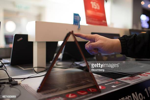 An employee demonstrates how to use a Lenovo Group Ltd IdeaPad Yogo 2 Pro for a photograph at a Lenovo store in the Sha Tin district of Hong Kong...