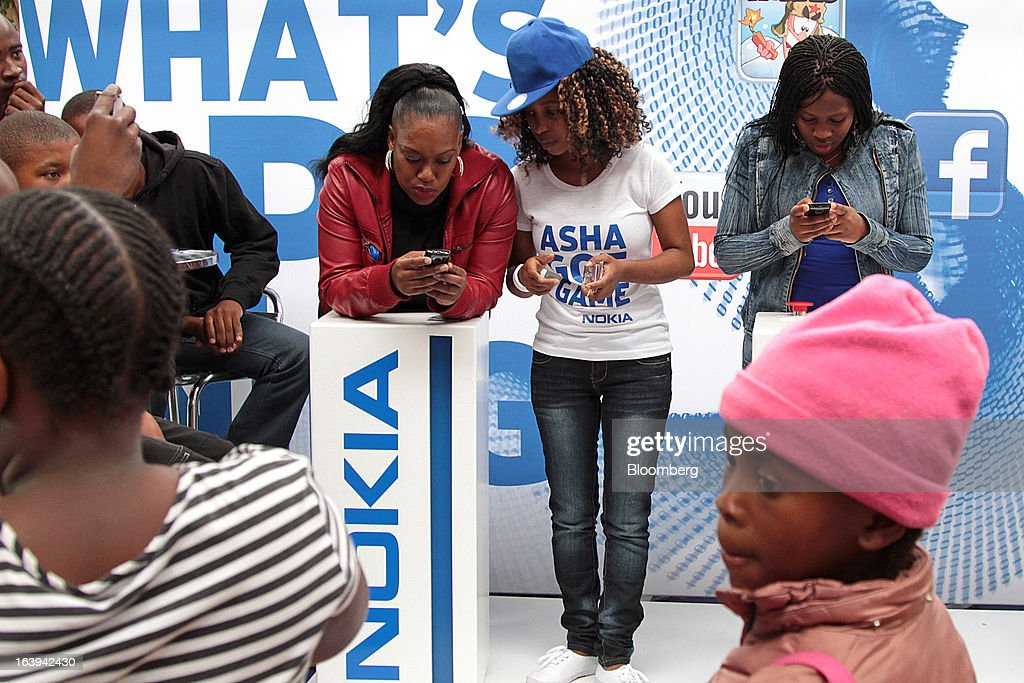 An employee demonstrates Nokia Asha smartphones to potential customers during a promotional 'activation day' event by Nokia Oyj in Maponya Mall in Soweto, South Africa, on Saturday, March 16, 2013. Nokia, based in Espoo, Finland, introduced three phones for its Asha line, sold primarily in emerging markets. Photographer: Nadine Hutton/Bloomberg via Getty Images
