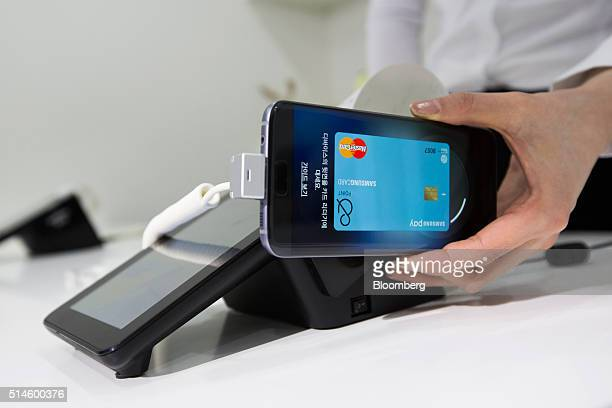 An employee demonstrates Samsung Pay using a Samsung Electronics Co Galaxy S7 smartphone during a media event in Seoul South Korea on Thursday March...