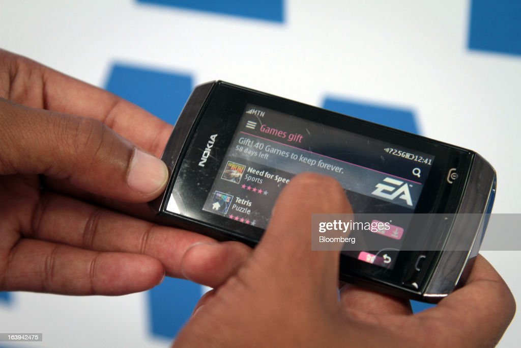 An employee demonstrates the function of a Nokia Asha 306 handset during a promotional 'activation day' event by Nokia Oyj in Maponya Mall in Soweto, South Africa, on Saturday, March 16, 2013. Nokia, based in Espoo, Finland, introduced three phones for its Asha line, sold primarily in emerging markets. Photographer: Nadine Hutton/Bloomberg via Getty Images