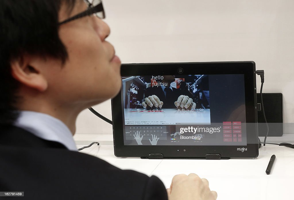 An employee demonstrates the gesture keyboard facility on a Stylistic Q572 tablet in the Fujitsu Ltd. pavilion at the Mobile World Congress in Barcelona, Spain, on Wednesday, Feb. 27, 2013. The Mobile World Congress, where 1,500 exhibitors converge to discuss the future of wireless communication, is a global showcase for the mobile technology industry and runs from Feb. 25 through Feb. 28. Photographer: Simon Dawson/Bloomberg via Getty Images