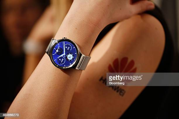 An employee demonstrates the new Huawei Watch wearable device during a Huawei Technologies Co news conference ahead of the Mobile World Congress in...