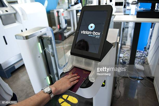 An employee demonstrates the passport scanning function on an automated border control eGate system based on facial recognition at the VisionBox...