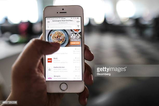 An employee demonstrates the Tiny Owl application on a smartphone for a photograph at the company's head office in Mumbai India on Monday March 9...