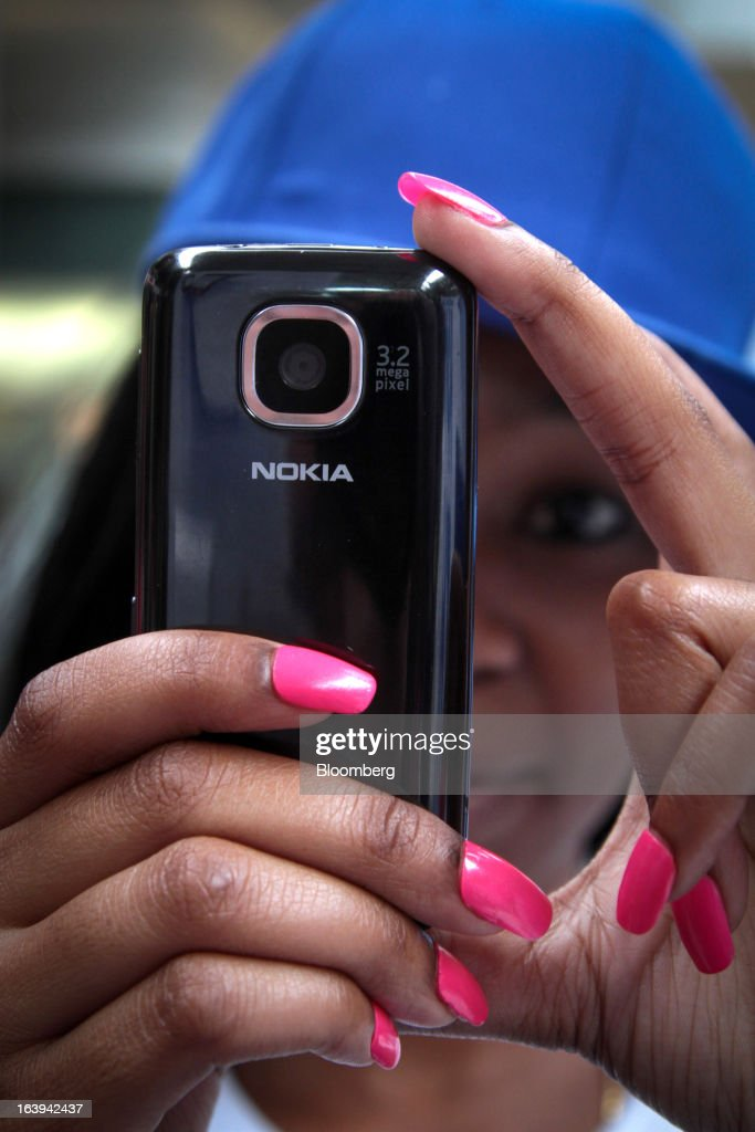 An employee demonstrates the use of a new Nokia Asha 311 smartphone during a promotional 'activation day' event by Nokia Oyj in Maponya Mall in Soweto, South Africa, on Saturday, March 16, 2013. Nokia, based in Espoo, Finland, introduced three phones for its Asha line, sold primarily in emerging markets. Photographer: Nadine Hutton/Bloomberg via Getty Images