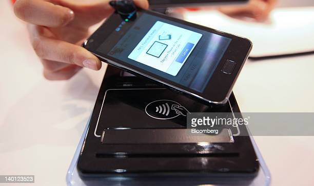 An employee demonstrates the use of a smartphone with an NFCenabled tagging point for wireless payment at the Mobile World Congress in Barcelona...