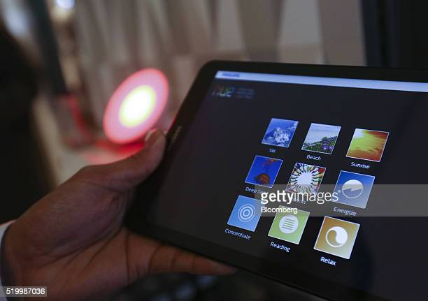 An employee demonstrates the use of the Philips NV Hue personal lighting kit using a tablet device inside the Smart Home section at a John Lewis Plc...