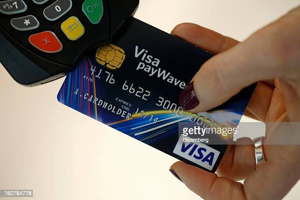 An employee demonstrates the Visa payWave contactless payment system for debit and credit cards at the Mobile World Congress in Barcelona Spain on...