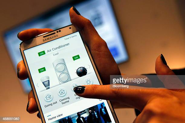 An employee demonstrates using the air conditioner control function of the Samsung Smart Home system with a smartphone at the Samsung Innovation...