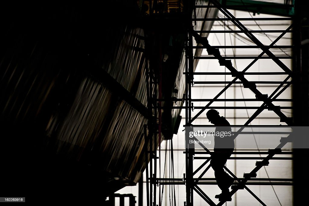 An employee descends scaffolding surrounding a U.S. Navy Littoral Combat Ship (LCS) under construction at Marinette Marine Corp., in Marinette, Wisconsin, U.S., on Monday, Feb. 11, 2013. Marinette Marine Corp. makes one version of the Littoral Combat Ship in partnership with Lockheed Martin Corp. As the Pentagon faces $500 billion in spending cuts over a decade that are set to begin March 1, the $37 billion program to design and build Littoral Combat Ships may become a target for reductions that would take business from Lockheed and Austal Ltd., which also makes a version of the ship in partnership with General Dynamics Corp. at Austal's yard in Mobile, Alabama. Photographer: Daniel Acker/Bloomberg via Getty Images