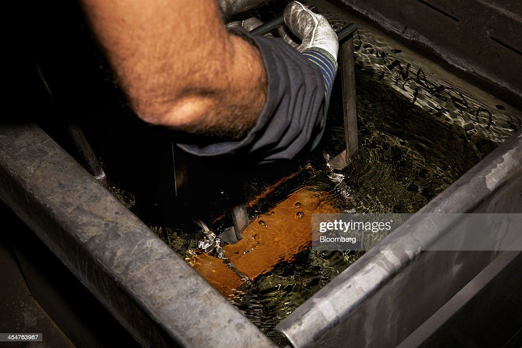 An employee dips a newly manufactured 400 ounce gold bar in water to cool it during the semiautomated gold bar manufacturing process at a precious...