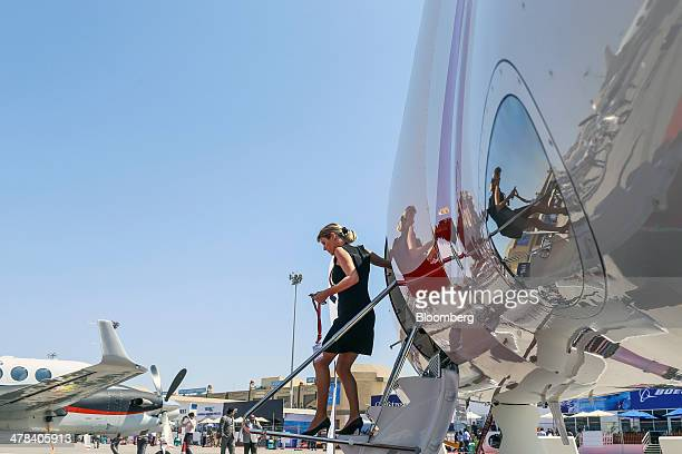 An employee disembarks a Dassault Aviation SA Falcon 7X aircraft on display during the India Aviation 2014 air show held at the Begumpet Airport in...
