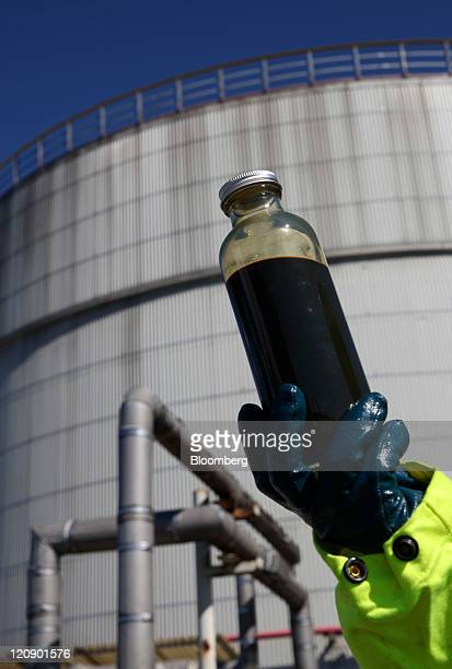 An employee displays a bottle of crude oil taken for testing in this arranged photograph at the Mongstad oil and gas refinery partowned by Statoil...