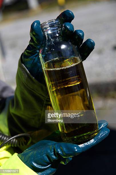 An employee displays a bottled sample of diesel oil at the Mongstad oil and gas refinery largely owned by Statoil ASA near Bergen Norway on Thursday...