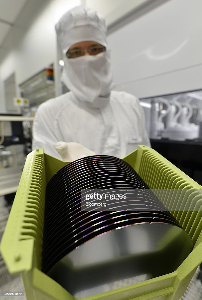 An employee displays a box of Infineon Technologies AG semiconductor wafers for a photograph in a sterile room at the company's factory in Regensburg, Germany, on Tuesday, Jan. 29, 2013. Infineon Technologies AG, Germanys largest chipmaker, agreed to buy International Rectifier Corp. for about $3 billion in cash, adding to its power-management technology business. Photographer: Guenter Schiffmann/Bloomberg via Getty Images