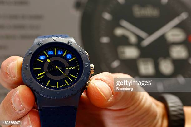 An employee displays a Cogito Pop Blue Electric smartwatch produced by ConnecteDevice Ltd designed to connect to an app on the wearer's smartphone at...