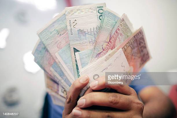 An employee displays a fan of mixed denomination Swedish kronor notes in this arranged photograph at a Travelex store operated by Travelex Holdings...