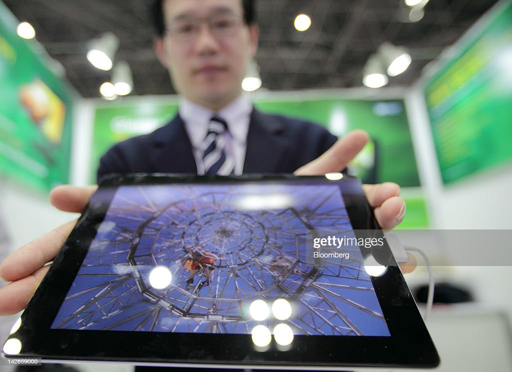 An employee displays a glasses-free 3-D liquid crystal display (LCD) in the 3DIS Co. booth at the Finetech Japan exhibition in Tokyo, Japan, on Wednesday, April 11, 2012. Finetech Japan, the world's largest flat panel display exhibition, will be held through April 13. Photographer: Tomohiro Ohsumi/Bloomberg via Getty Images