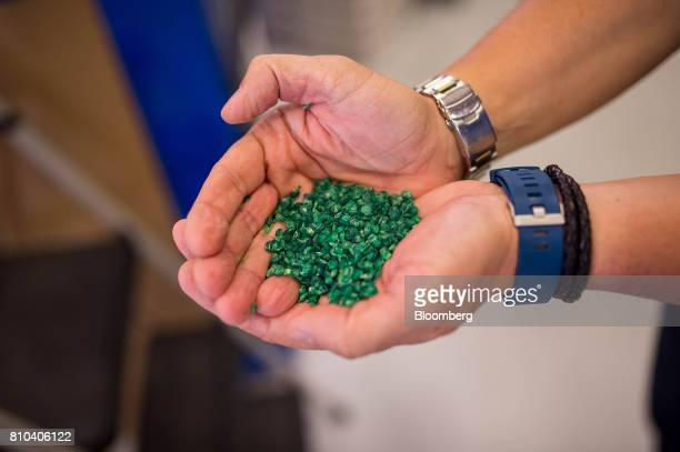 An employee displays a handful of the plastic pellets to be melted down to form vinyl records at the Precision Record Pressing facility in Burlington...