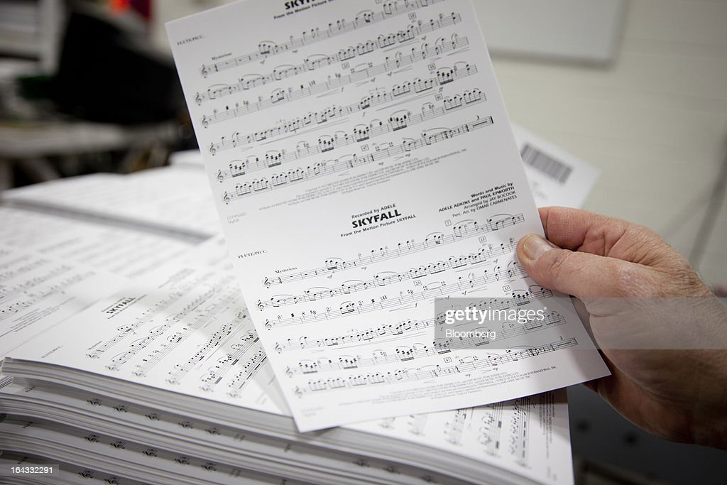 An employee displays a page of marching band sheet music for the 'Skyfall' movie score at the Hal Leonard Corp. printing facility in Winona, Minnesota, U.S., on Friday, March 22, 2013. Hal Leonard is the world's largest print music publisher, distributing more than 200,000 titles to over 65 countries. Photographer: Ariana Lindquist/Bloomberg via Getty Images