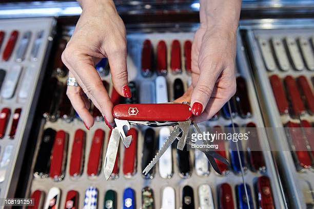 An employee displays a Swiss army penknife for sale at the Victorinox AG factory store in Ibach Switzerland on Thursday Jan 20 2011 Victorinox...