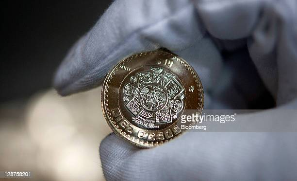 An employee displays a ten peso coin for a photograph at the Mexican Mint also known as Casa de Moneda in San Luis Potosi Mexico on Wednesday Oct 5...