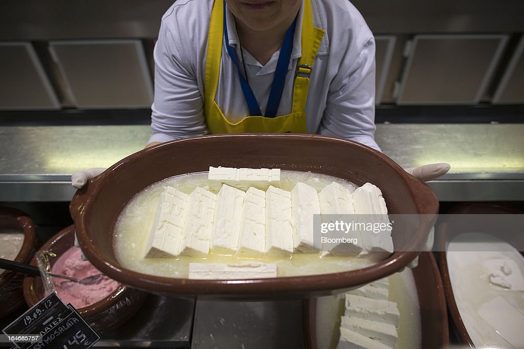 An employee displays a tray of feta cheese inside a Carrefour SA supermarket at the Mall of Cyprus in Nicosia, Cyprus, on Tuesday, March 26, 2013. Controls on capital movements to prevent money from draining out of the banking system -- allowed in exceptional circumstances under European Union law -- will remain for 'a matter of weeks,' Cypriot Finance Minister Michael Sarris said. Photographer: Simon Dawson/Bloomberg via Getty Images