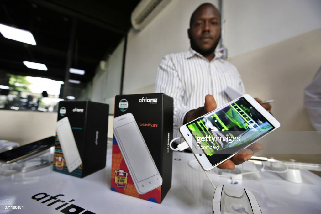 An employee displays an AfriOne Gravity Z1 smartphone during a launch event at the new AfriOne Ltd. manufacturing plant in Lagos, Nigeria, on Friday, April 21, 2017. The plant has the capacity to produce some 120,000 units per month. Photographer: George Osodi/Bloomberg via Getty Images