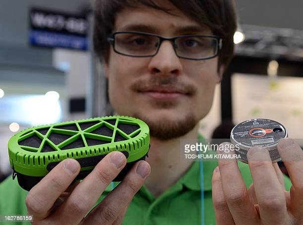 An employee displays myFC powerchargher and its fuel cell puck at the company's booth during the FC Expo in the World Smart Energy Week 2013 in Tokyo...