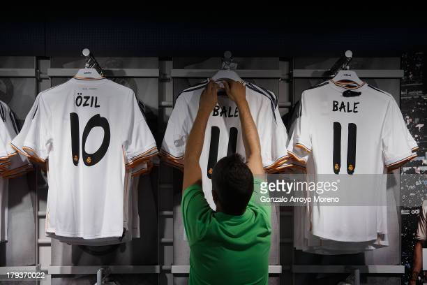 An employee displays new Gareth Bale Real Madrid shirts at the Real Madrid Oficcial Store alongside Mesut Ozil's shirt on the day Gareth Bale is...