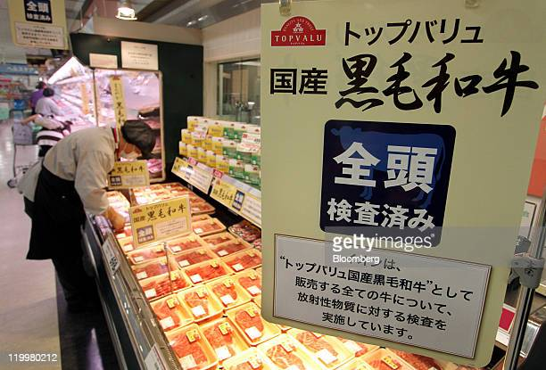 An employee displays packages of Wagyu beef sold under the Topvalu brand at an Aeon Co supermarket in Tokyo Japan on Thursday July 28 2011 Concern...